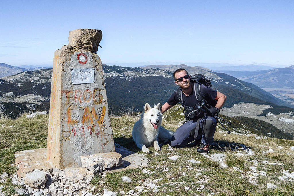 Ante Romac from Dinaric guides on Troglav peak with his dog